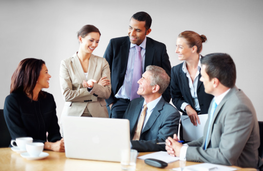 Business people discussing in meeting with laptop on desk
